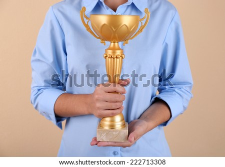 Woman holding trophy cup on color background #222713308