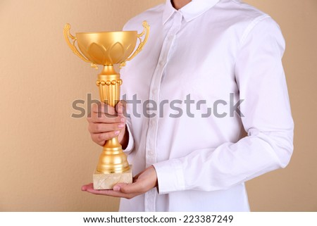 Woman holding trophy cup on color background #223387249