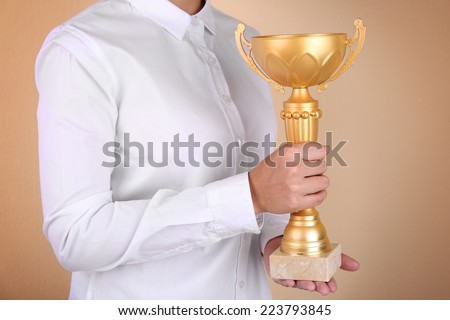 Woman holding trophy cup on color background #223793845