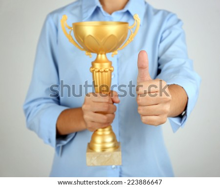 Woman holding trophy cup on color background #223886647