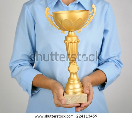 Woman holding trophy cup on color background #224113459