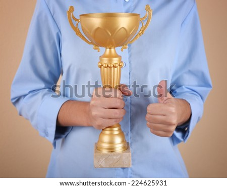 Woman holding trophy cup on color background #224625931