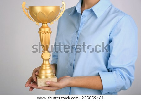 Woman holding trophy cup on color background #225059461