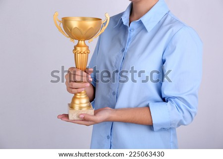 Woman holding trophy cup on color background #225063430
