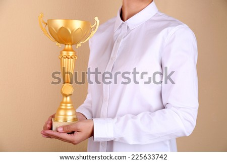 Woman holding trophy cup on color background #225633742