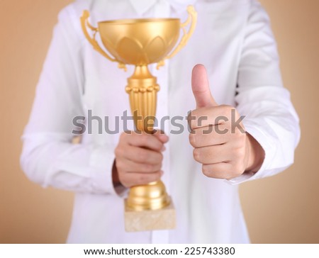 Woman holding trophy cup on color background #225743380
