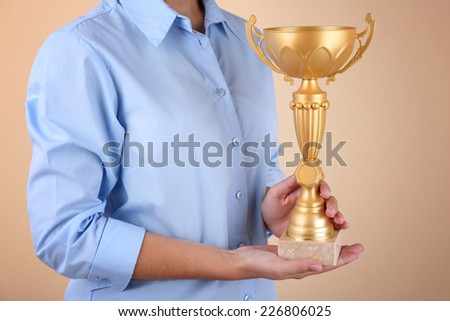 Woman holding trophy cup on color background #226806025
