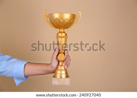 Woman holding trophy cup on color background #240927040