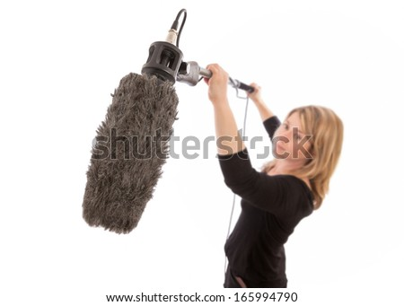 Woman holding up a microphone boom against a white background. Selective focus on the furry microphone  windshield.