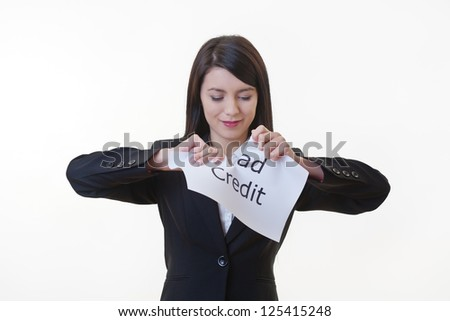 woman holding up a piece of paper with the words bad credit written on it and tearing the sheet of paper in half