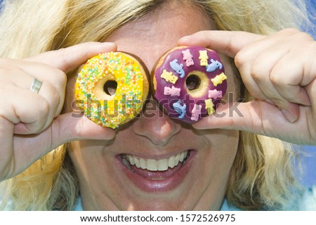 Woman holding up and looking through donuts