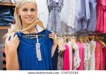 Woman holding up blue shirt and smiling in clothing store