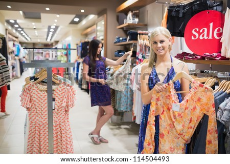 Woman holding up orange shirt in clothing store