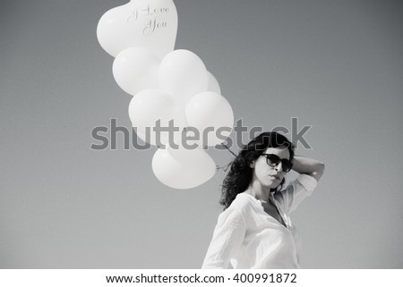 woman holding white balloons on seaside #400991872