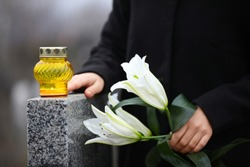 Woman holding white lilies near grey granite tombstone with candle outdoors, closeup. Funeral ceremony