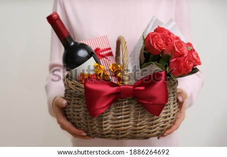 Woman holding wicker basket with gift, bouquet and wine on light grey background, closeup