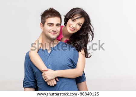 woman holding with love her boyfriend from behind, posing at camera