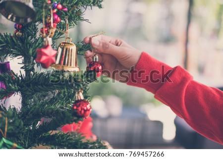 woman holding xmas ornament. girl decorate Christmas tree in a house. holiday celebration. season's greetings