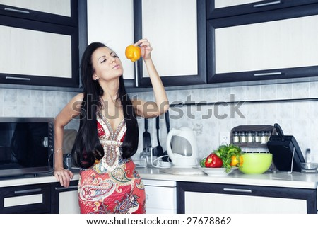 Woman holding yellow pepper in the kitchen
