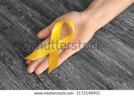 Woman holding yellow ribbon on wooden background. Cancer awareness concept #1172148901