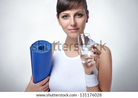 woman holding yoga mat and water