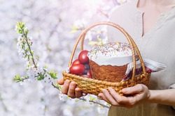 Woman holds a basket with Easter cake and eggs against the background of blooming cherry.