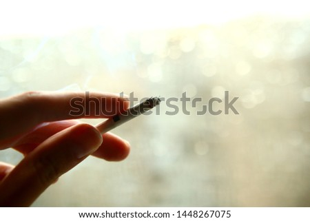 Woman holds a cigarette. Copy space for the text