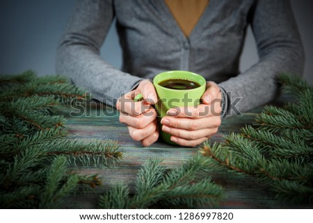 Woman holds a cup of hot tea among the fir branches. Cozy morning at home. With copy space #1286997820