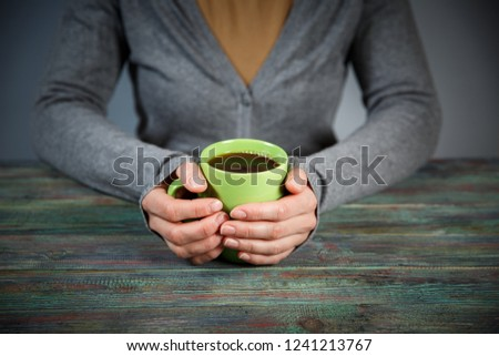 Woman holds a cup of hot tea. Cozy morning at home. With copy space #1241213767