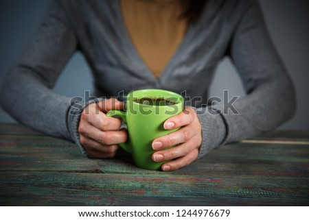 Woman holds a cup of hot tea. Cozy morning at home. With copy space #1244976679