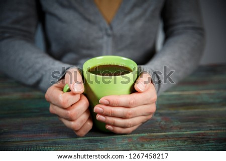 Woman holds a cup of hot tea. Cozy morning at home. With copy space #1267458217