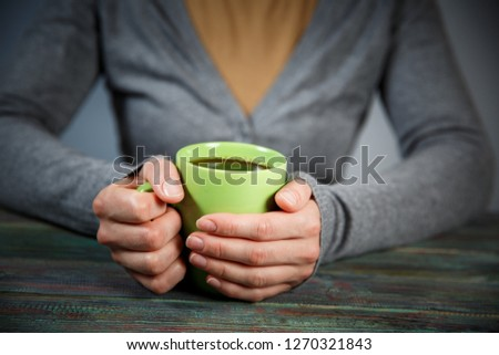 Woman holds a cup of hot tea. Cozy morning at home. With copy space #1270321843