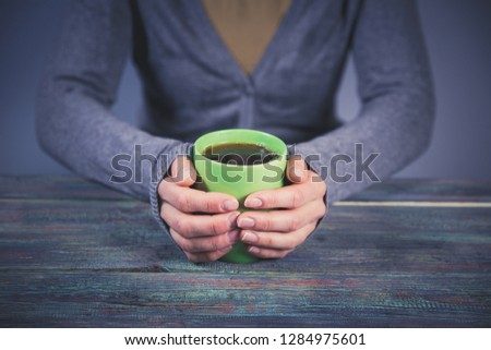Woman holds a cup of hot tea. Cozy morning at home. With copy space #1284975601