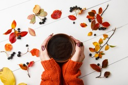 woman holds a cup of tea in hands on white wooden background with autumn leaves. Hot tea among fall leaves decor. Autumn holidays, family celebration, thanksgiving day, home weekend. warming drink