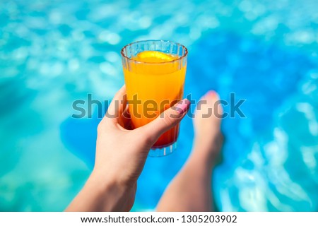 Female hand holds a glass with juice in pool Images and ...