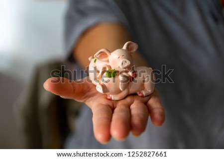 Woman holds a lucky charm in her hand, a lucky pig