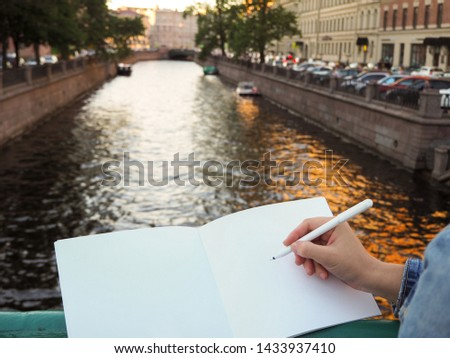 Woman holds a pen and white journal while standing on the bridge on the city river background. Mockup of person's hand holding blank notebook pages preparing to write down ideas and goals.