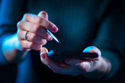 Woman holds a phone and a stylus in her hands. Hands of a girl with a stylus and a smartphone. Hands with phone close-up. Concept - sale of styluses for gadgets. Concept - styluses for touch gadgets.