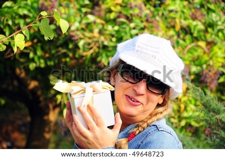 woman holds a white gift pack