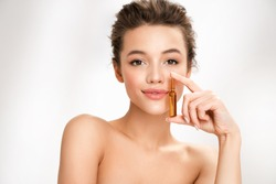 Woman holds ampoule with serum for hair or skin care. Photo of attractive woman with perfect makeup on white background. Beauty concept