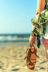 Woman holds brown leather sandals in her hand and looks at the sea. Early morning at the seashore