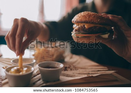 woman holds burger with hands...