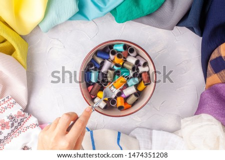 Woman holds fork with spool of thread under the bowl with spools in fabric multi-colored frame on grey background #1474351208