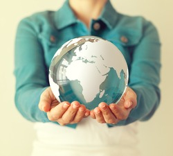 Woman holds glass earth in her hands. Globe