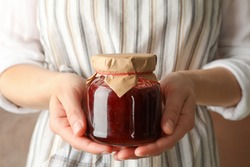 Woman holds glass jar with strawberry jam, close up
