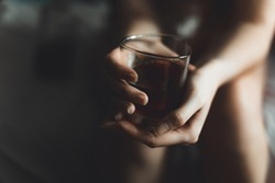 woman holds glass with whiskey. alcohol cocktail in glass. woman's alcoholism, alcohol addict concept