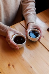 woman holds in hands two ceramic mug with black coffee. alternative brewing method of specialty coffee. background light wood. coffee shop interior