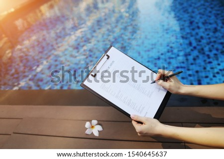 woman holds pen and visa application in UAE Dubai, contributes her data for new trip to foreign country. concept of signing papers, traveling to other countries. Front used with Open Font License