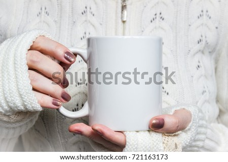 Woman holds white mug in hands. Design Mockup for winter holidays #721163173