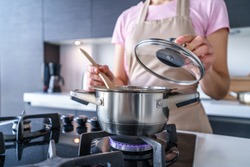 Woman housewife in apron using steel metal saucepan for preparing dinner in the kitchen at home. Kitchenware for cooking food